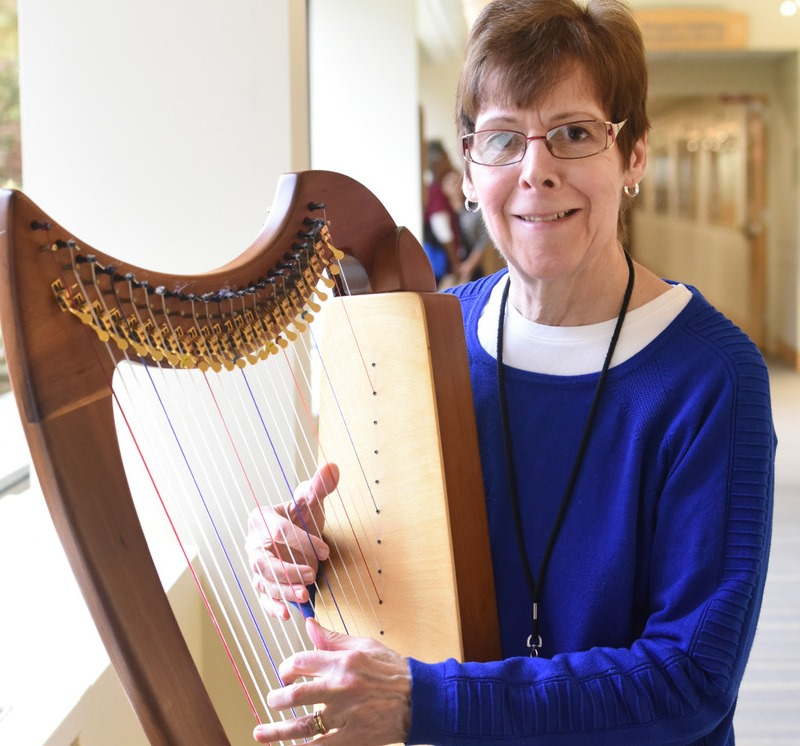 Adult volunteer playing harp