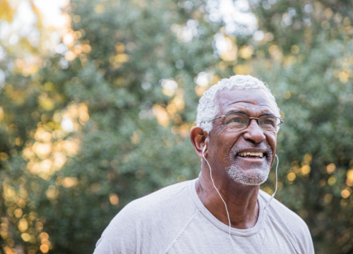 older Black man exercising outdoors with headphones